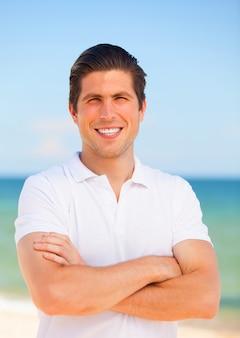 Przystojny młody człowiek przy plażowym tłem