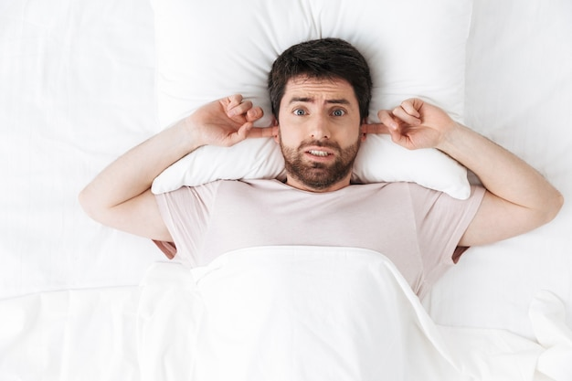 Przystojny młody człowiek rano pod kocem w łóżku leży zakrywając uszy