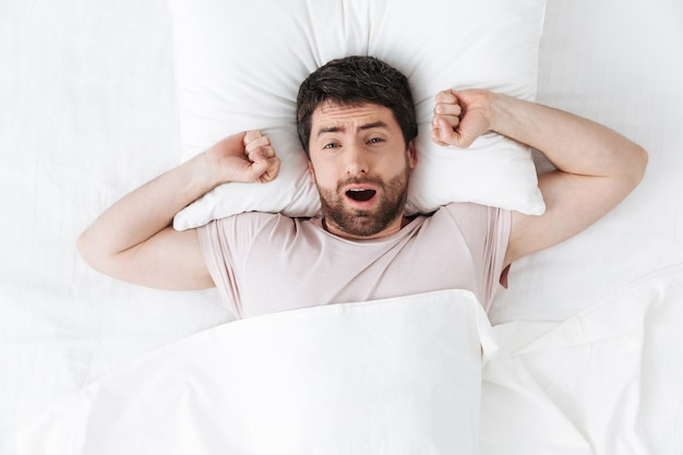 Przystojny młody człowiek rano ziewanie i rozciąganie w łóżku