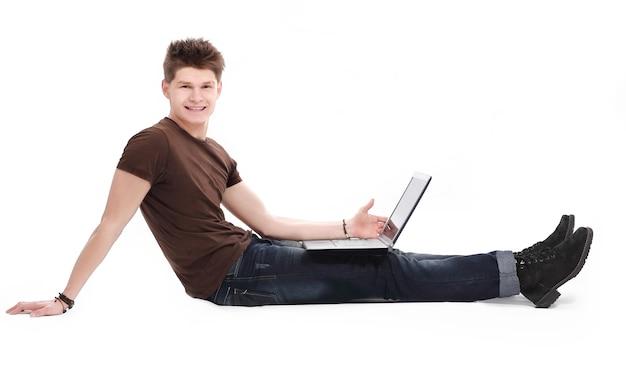 Przystojny młody człowiek relaksujący za pomocą laptopa i leżąc na kanapie. koncepcja freelancingu