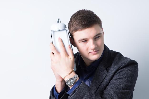 Przystojny młody człowiek słuchając budzika blisko ucha poważnie, na białym tle.