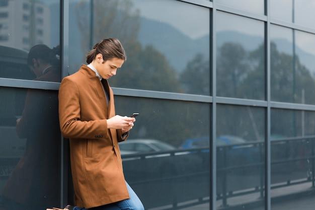 Przystojny młody człowiek sprawdza jego telefon