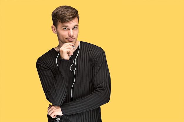 Przystojny młody człowiek stoi i słucha muzyki. atrakcyjny mężczyzna trzyma słuchawki i telefon komórkowy na żółtym tle