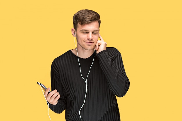 Przystojny młody człowiek stoi i słucha muzyki.