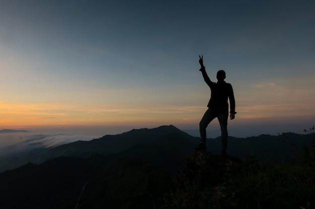 Przystojny młody człowiek stojący za dwoma palcami, aby pokazać siłę, aby kontynuować walkę.