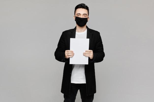Przystojny młody człowiek trzyma białą prześcieradło w czarnej masce ochronnej
