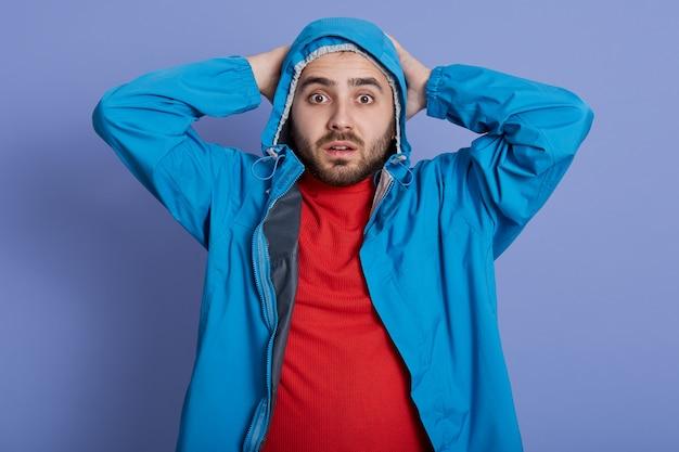 Przystojny młody człowiek ubrany w niebieski płaszcz i czerwoną koszulę, stojąc i dotykając głową, patrząc bezpośrednio na aparat z wielkimi oczami