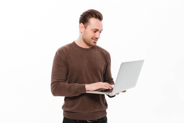 Przystojny młody człowiek używa laptop.