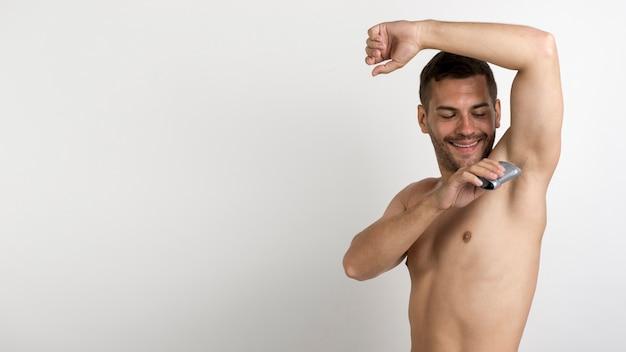 Przystojny młody człowiek używa rolkę na dezodorant pozyci przeciw białemu tłu