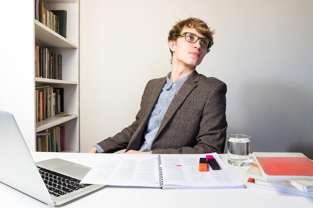 Przystojny młody człowiek w czytaniu okularów w nowoczesnym minimalistycznym miejscu pracy