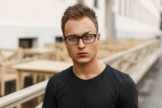 Przystojny, młody człowiek w okularach w czarnej koszuli stojący na ulicy.