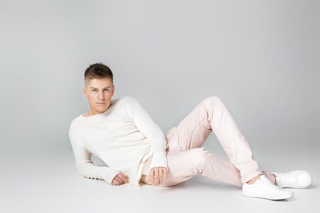 Przystojny, młody człowiek w pozuje biały sweter