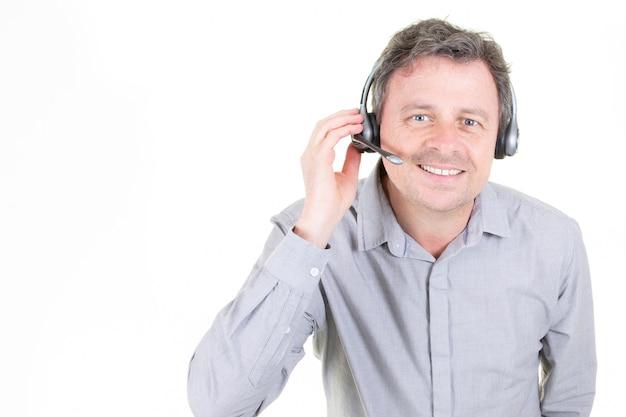 Przystojny młody człowiek w pracy w centrum telefonicznym z hełmofonami na bielu z kopii przestrzenią