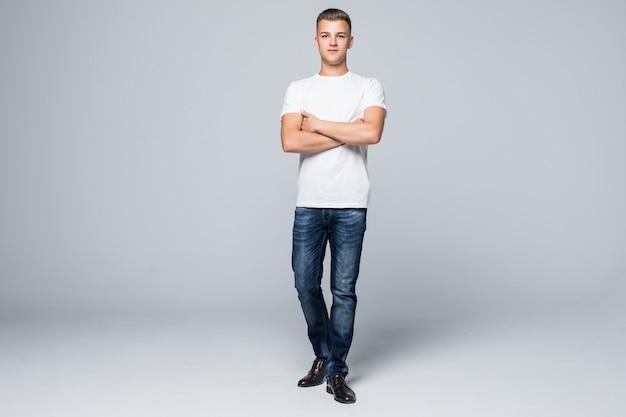Przystojny młody człowiek w stylu casual, odzież białą koszulkę i niebieskie dżinsy na białym tle