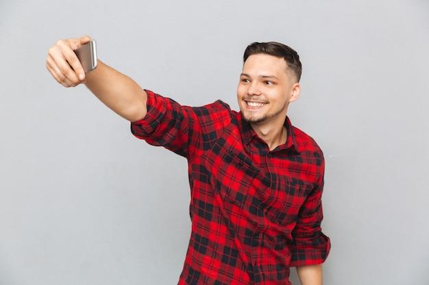 Przystojny młody człowiek w szkockiej kraty koszula robi selfie