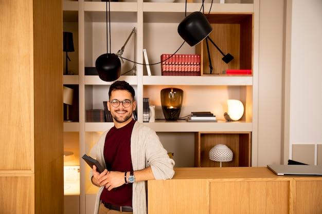 Przystojny młody człowiek w ubranie i okulary trzyma książkę w domu