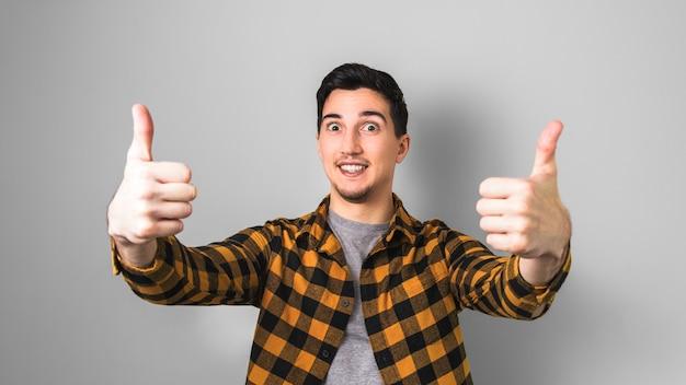 Przystojny młody człowiek w żółtej koszuli pokazuje obiema rękami aprobaty jak gest przeciw popielatemu koloru tłu