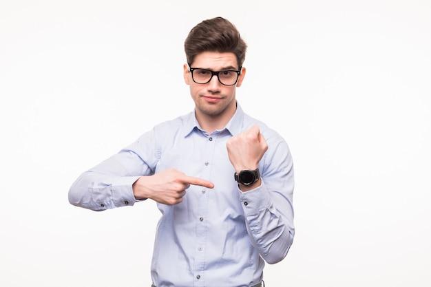 Przystojny młody człowiek wskazuje przy jego mądrze zegarkiem odizolowywającym na biel przestrzeni.