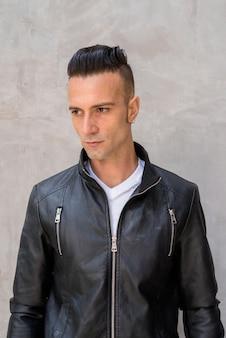 Przystojny młody człowiek z podcięciem na sobie czarną skórzaną kurtkę