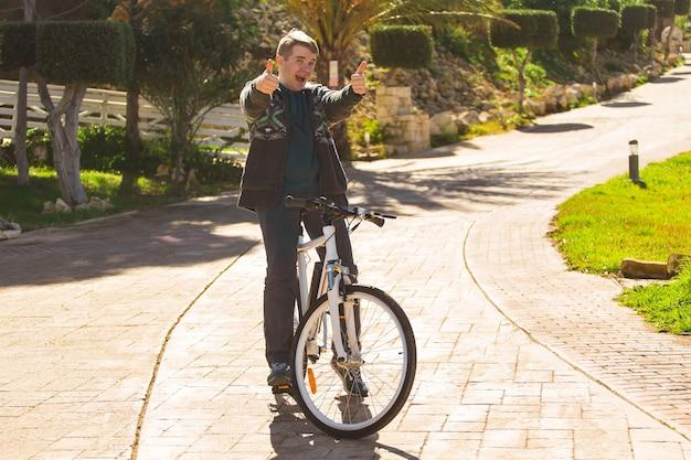 Przystojny młody człowiek z rowerem pokazuje kciuki w parku w słoneczny dzień