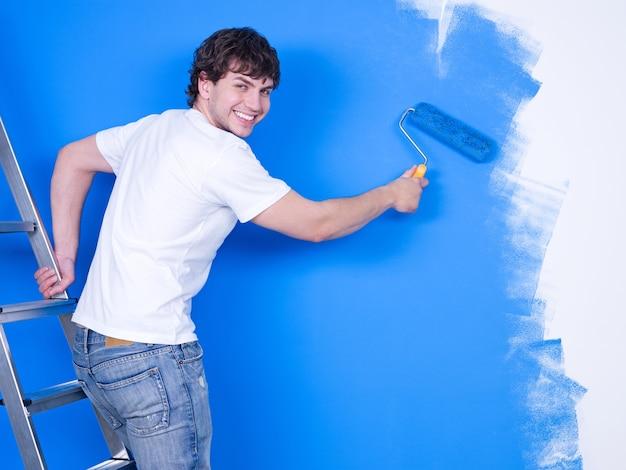Przystojny młody człowiek z szczęśliwym uśmiechem maluje ścianę