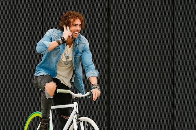 Przystojny młody człowiek z telefonem komórkowym i rowerem na stałe na ulicy.