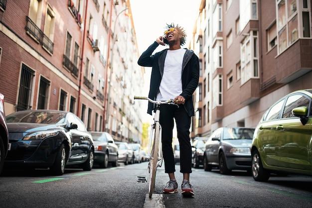 Przystojny młody człowiek za pomocą telefonu komórkowego i roweru stacjonarnego na ulicy.
