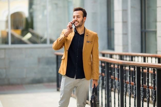 Przystojny, młody, dorosły mężczyzna w garniturze rozmawia przez telefon gestem ręki