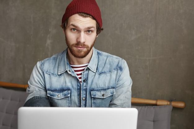 Przystojny młody freelancer z brodą na sobie dżinsową kurtkę i bordowy kapelusz siedzi w kawiarni