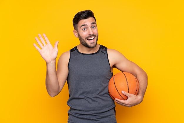 Przystojny młody gracz koszykówki mężczyzna nad odosobnioną biel ścianą salutuje z ręką z szczęśliwym wyrażeniem