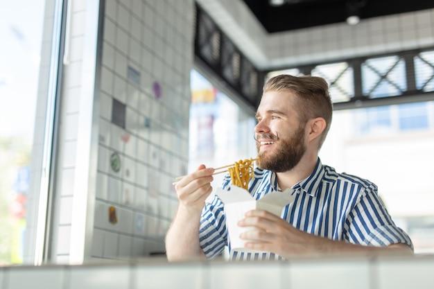 Przystojny młody hipster facet je chiński makaron za pomocą drewnianych pałeczek, siedząc w kawiarni i patrząc przez okno. koncepcja kuchni azjatyckiej.