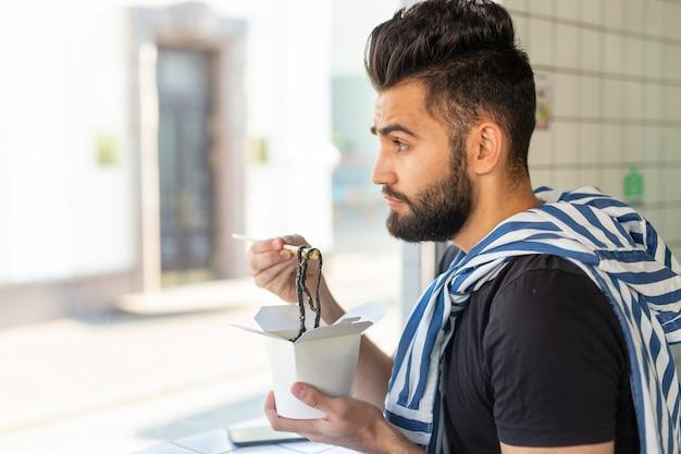 Przystojny młody hipster facet je chiński makaron za pomocą drewnianych pałeczek, siedząc w kawiarni i patrząc w okno. koncepcja kuchni azjatyckiej.