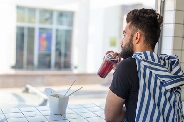 Przystojny młody hipster facet picia koktajl w kawiarni i patrząc w okno.