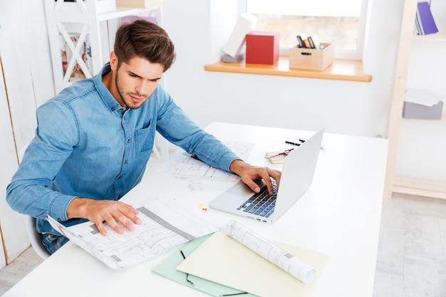 Przystojny młody inteligentny biznesmen pracujący z dokumentami i komputerem w biurze