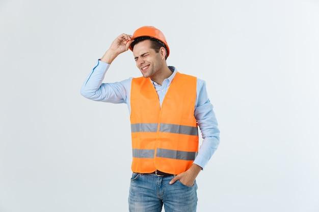 Przystojny młody inżynier mężczyzna na białym tle noszący kask ochronny z poważną twarzą i ręką zszokowany wstydem za błąd, wyraz strachu, przestraszony w ciszy, tajna koncepcja