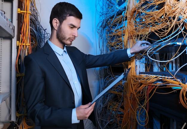Przystojny młody inżynier pracujący w serwerowni