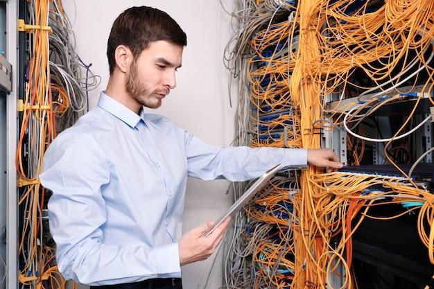 Przystojny młody inżynier z komputerem typu tablet pracujący w serwerowni