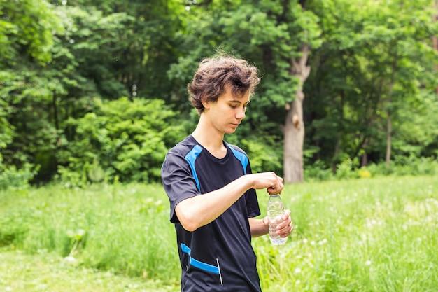 Przystojny młody jogger wody pitnej po ciężkim wysiłku w ogrodzie