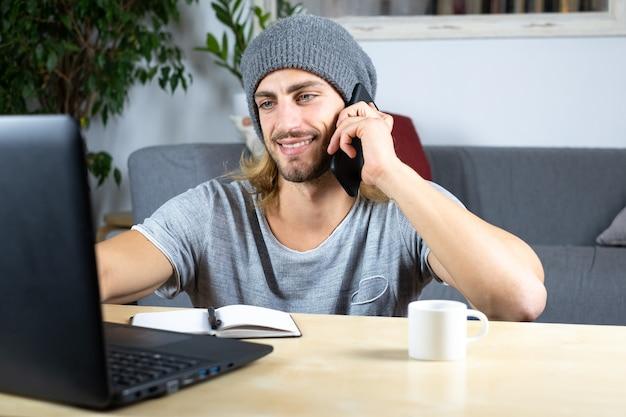 Przystojny młody kaukaski mężczyzna przy użyciu komputera pracującego w domu i rozmawiając z telefonem czuje się szczęśliwy