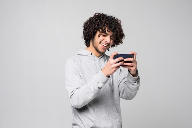 Przystojny młody kędzierzawy mężczyzna używa smartphone nad szarości ścianą