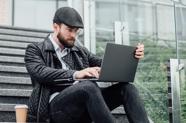 Przystojny młody kierownik mężczyzna pije kawę i pracuje na laptopie, siedząc na zewnątrz na schodach
