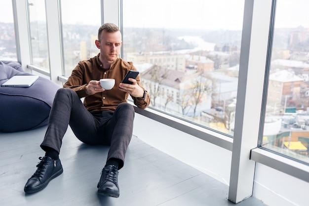 Przystojny młody kierownik siedzi na podłodze z telefonem w pobliżu panoramicznego okna