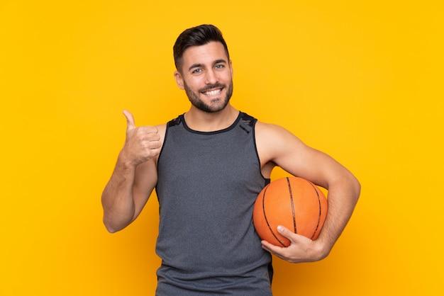 Przystojny młody koszykarz mężczyzna na pojedyncze białe ściany z kciuki do góry, ponieważ stało się coś dobrego