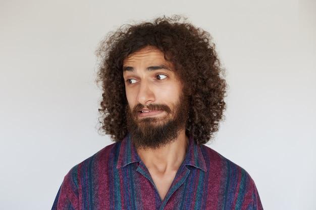 Przystojny, młody, kręcony brunet z brodą patrząc na bok ze zmieszaną twarzą i wykrzywionymi ustami, ubrany w pasiastą, wielokolorową koszulę