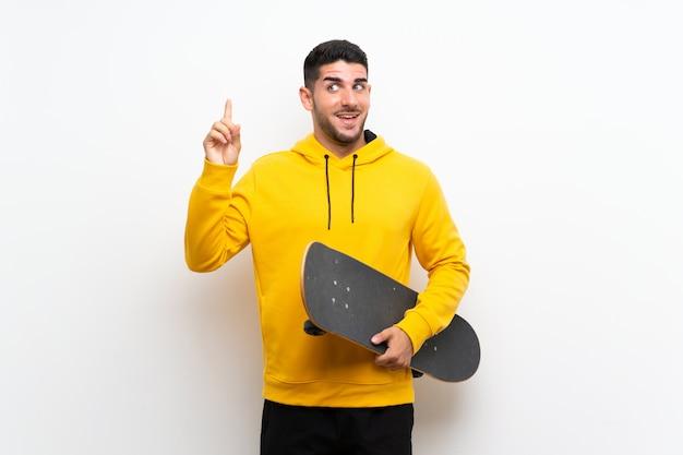 Przystojny młody łyżwiarz mężczyzna nad odosobnioną biel ścianą zamierza realizować rozwiązanie podczas gdy podnoszący palec w górę