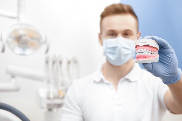 Przystojny młody męski dentysta demonstruje zęby foremkę