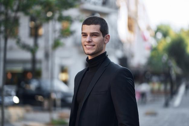 Przystojny młody męski odprowadzenie na ulicie