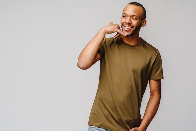 Przystojny młody mężczyzna afroamerykanów pokazujący znak wywoławczy i uśmiechnięty stojącco na szarej ścianie