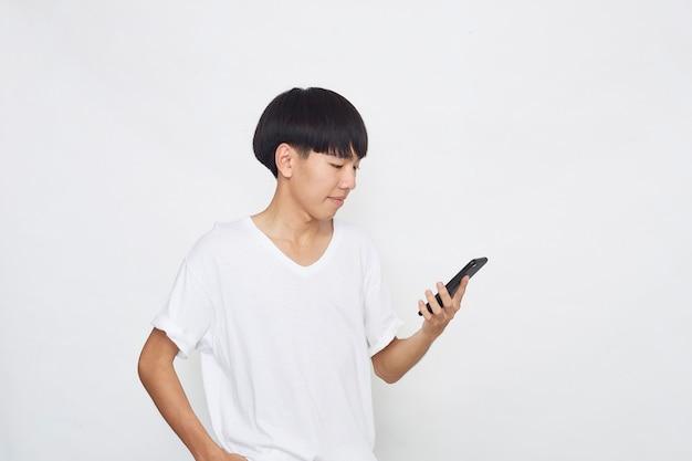 Przystojny Młody Mężczyzna Azjatyckich Przedstawiający Telefon Do Pustej Przestrzeni Na Białym Tle Białej Powierzchni Premium Zdjęcia