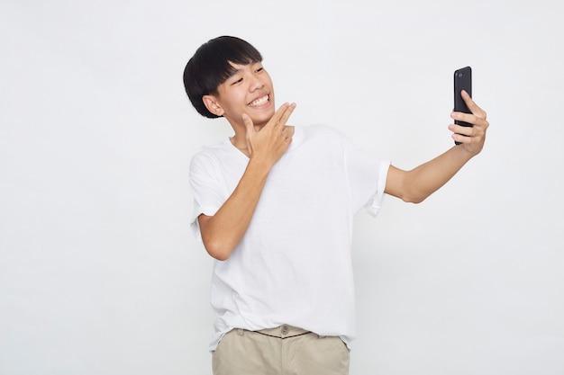 Przystojny młody mężczyzna azjatyckich przedstawiający telefon do pustej przestrzeni na białym tle białej powierzchni